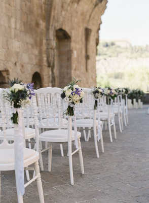 wedding ceremony in italy stone ruins white chairs greenery white purple flowers along aisle