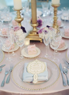 Gold beaded charger plate with light blue napkin, personalized menu card, and pink favor box