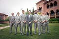 Groomsmen in grey suits with light green ties and natural boutonnieres groom in darker grey suit