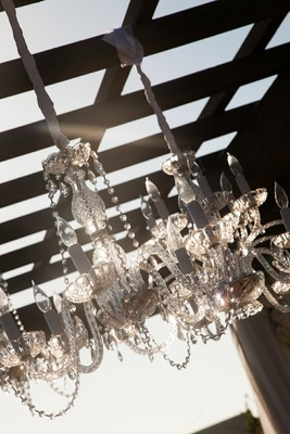 Fancy crystal chandelier hanging from ceremony structure