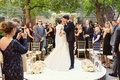 bride and groom share kiss platform in middle of outdoor aisle low roses after vows