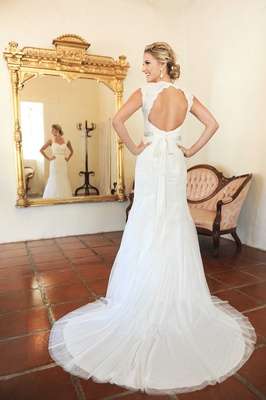 Jenna Reeves wearing a sleeveless wedding dress with keyhole back queen ann neckline and silk ribbon