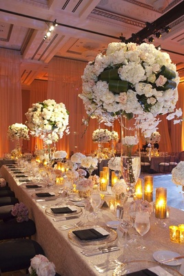 Wedding reception table with tall light floral arrangements and candles in golden hurricanes