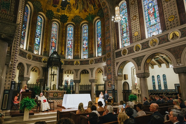 catholic church wedding with tall ceilings and stained glass windows