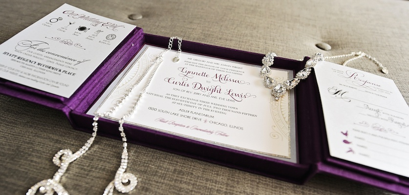 Bride's rhinestone headdress and necklace on purple gatefold wedding invitation box