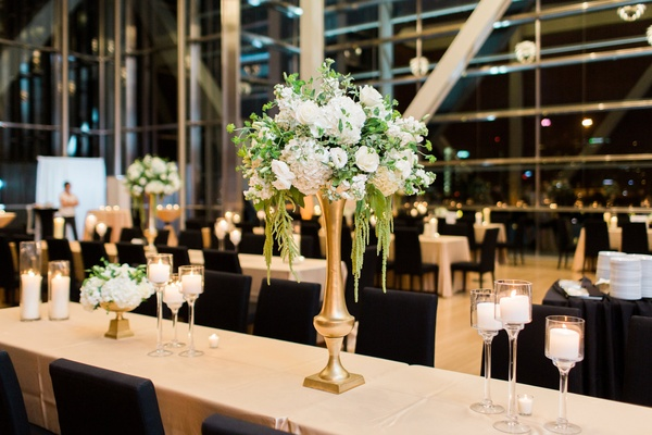tall centerpiece with white hydrangeas, greenery and amaranths, gold base, long table