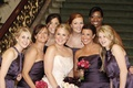 Bride in a strapless Amsale gown with bridesmaids in dark purple dresses