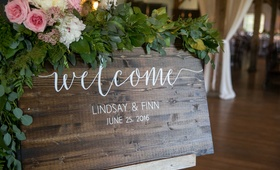 welcome sign on wood plaque greenery pink white flower white writing