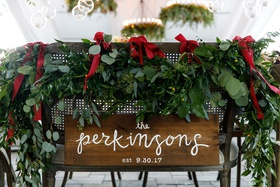 wedding reception seating cane back chair wood sign calligraphy garland red ribbon wedding ideas