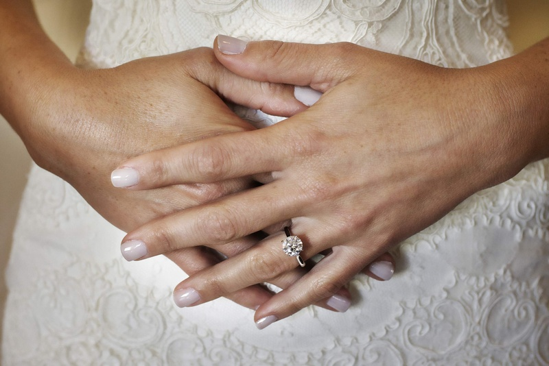 Bride's wedding manicure with round diamond engagement ring
