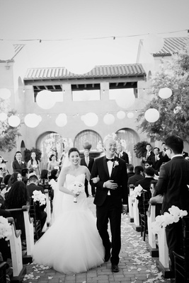 black and white photo of bride in romona keveza dress, groom in tux, paper lantern decor