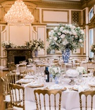 wedding reception historic ballroom blue white vase greenery white flowers gold chairs ornate