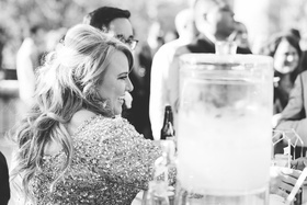 Black and white photo of bride groom serving drinks to friends and family before wedding ceremony