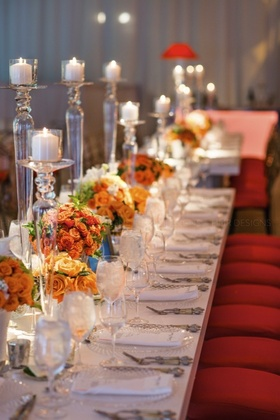 Bold pops of orange floral complement clean white linens and soft candlelight.