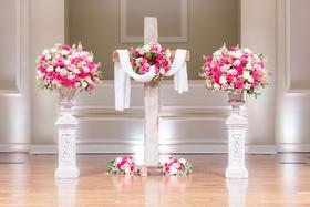 wedding ceremony church altar wood cross pink white flowers urns
