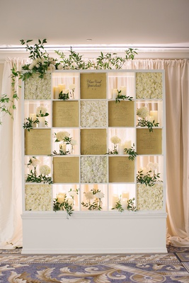 wedding reception seating chart square bookcase paper seating chart white roses flowers candles