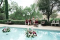 bride in flowy floral robe, bridesmaids in burgundy velvet robes, pool with floating florals