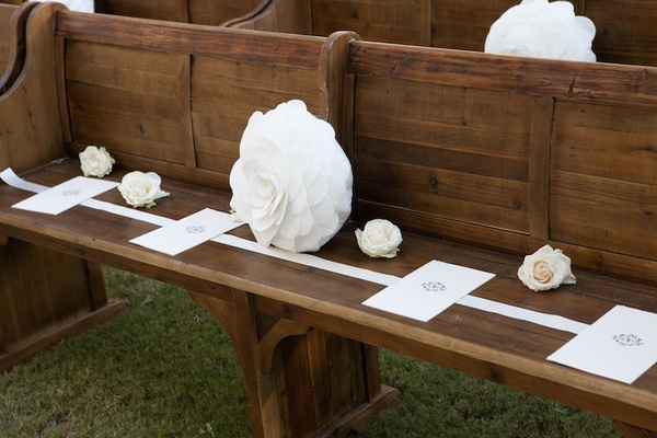 White programs and roses on wood church pew at outdoor wedding