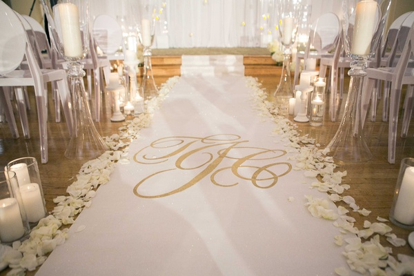 White aisle runner with gold monogram by The Original Runner Co with candles and flower petals