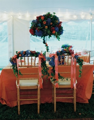 Couple's table with orange linen and blue flower centerpiece