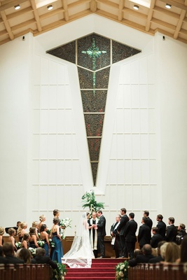 Bride and groom at altar top of red stairs guests in church pews wedding party tall ceiling wood