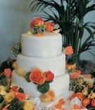 orange roses and lemon and orange wedges adorn white cake