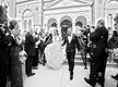 black and white photo of newlyweds exiting the church with bubbles blown at them