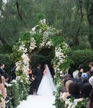 Bride in Monique Lhuillier wedding dress under chuppah of greenery and white flowers garlands hedge