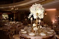 Round reception table with tablecloth and tall centerpiece flower arrangement white hydrangea orchid