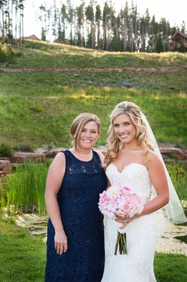 Bride in strapless Watters wedding dress with mother of bride in pearls and blue dress