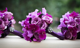 Bright purple nosegays with orchid, rose, and brooch