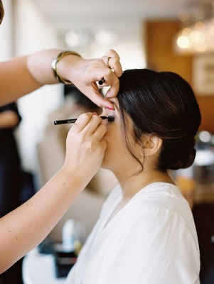 Bride with updo getting eye liner put on by makeup artist in white robe