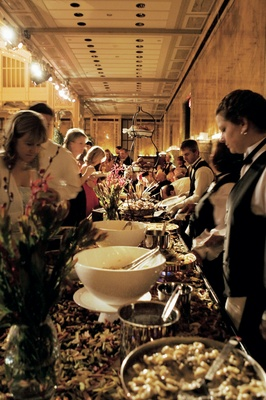 Guests and caterers at buffet style station