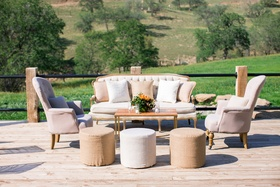 Arm chairs and couches on wood plank flooring in countryside