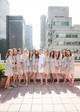 a bride and bridesmaids sporting silver and white robes pose on an NYC rooftop