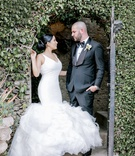 bride in ines di santo wedding dress, v-neck fit-and-flare gown with full ruffles, groom in tuxedo