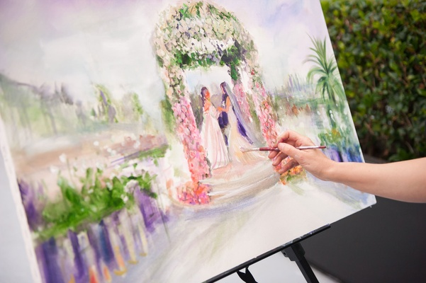 Brides standing under ceremony structure in canvas painting live event painter at wedding ceremony