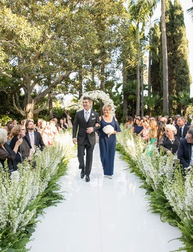 Mother's attire mother of groom in navy blue dress open shoulder detail white bouquet guests flowers