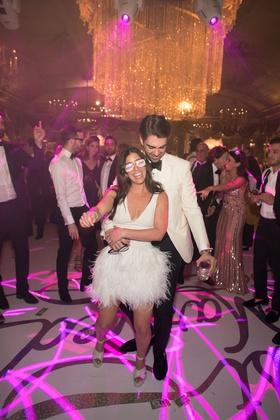 Bride in v-neck short wedding dress ostrich feather skirt high heels pink neon lighting on dance