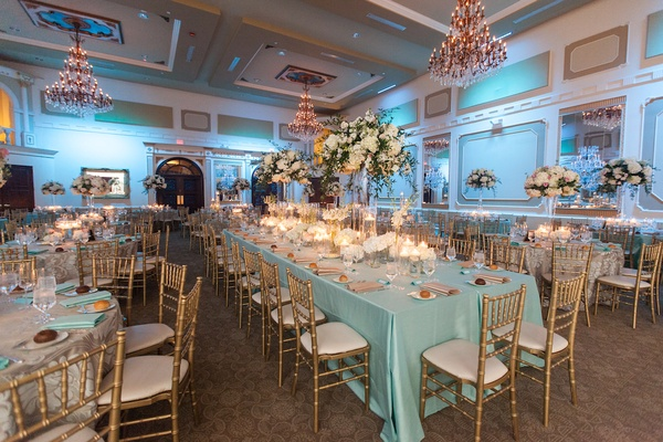 Gold chairs around long table with blue tablecloth