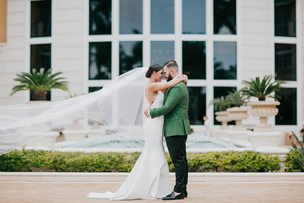 bride in crepe low back wedding dress cathedral veil groom in green tuxedo jacket miami wedding