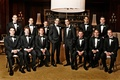 Groom with 12 groomsmen in black tuxedos and bow ties
