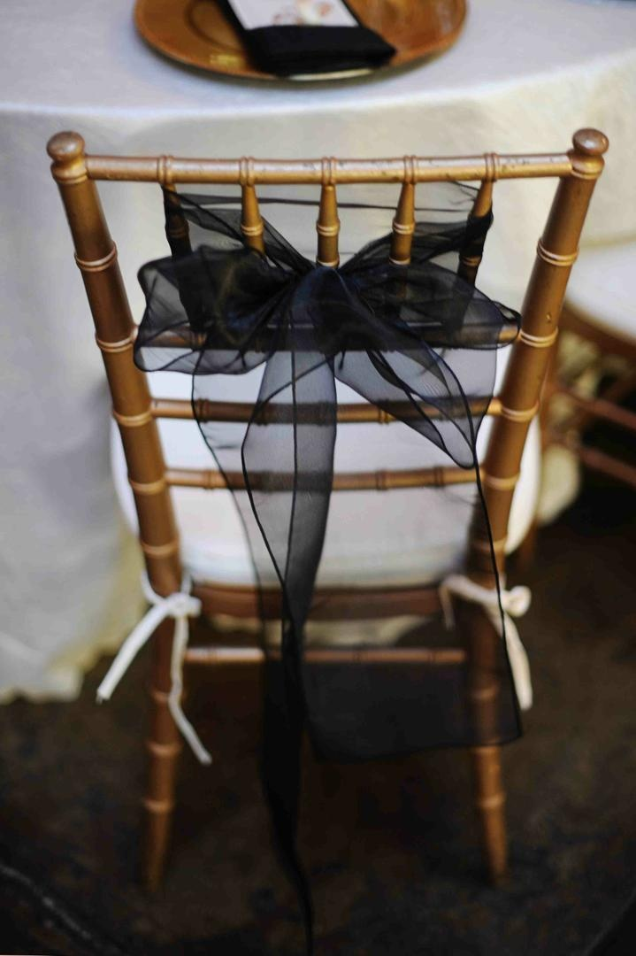Gold chair with white cushion and black ribbon decoration