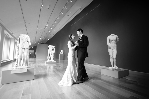 Black and white photo of bride and groom in room with statues art institute of chicago wood floor