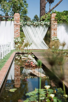 wedding ceremony belmond el encanto pond flowers lilies along aisle white drapery flowers