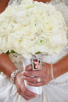 Bride's bouquet of white peonies, roses, ranunculuses, crystals, photo of her father kissing her
