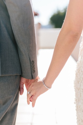 close up of bride and groom holding hands, bride wearing diamond tennis bracelet, halo engagement