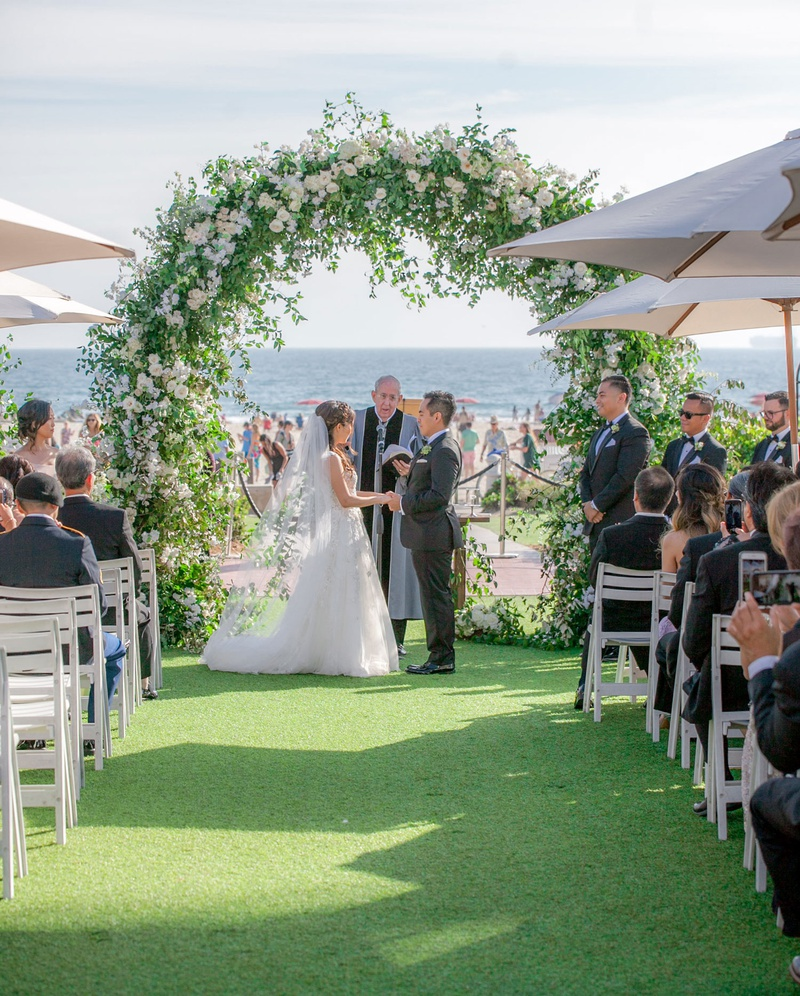 wedding ceremony on grass lawn near beach ocean san diego coronado island umbrella greenery arch