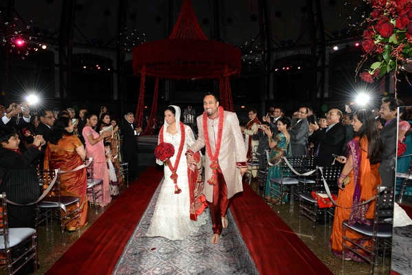 Indian newlyweds walking up damask aisle