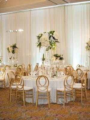 Round white table gold back oval chairs tall centerpiece white roses, amaranthus, monstera leaves
